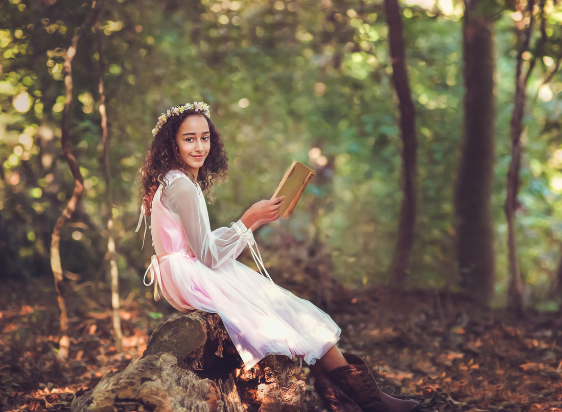 Girl in a gown and flower crown reading a vintage book in the woods